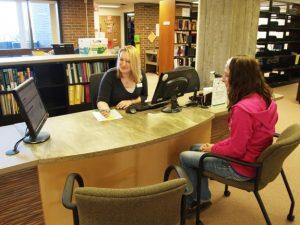 Bibliotecaria antendiendo a un usuario